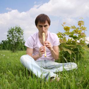 moški igra flavto na travi