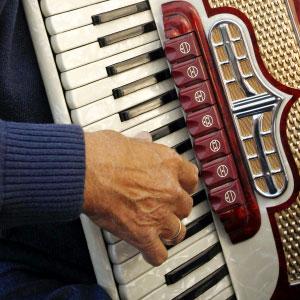 človek igra klavirsko harmoniko