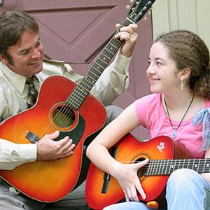 očka uči igrati kitaro hčerko z akordi
